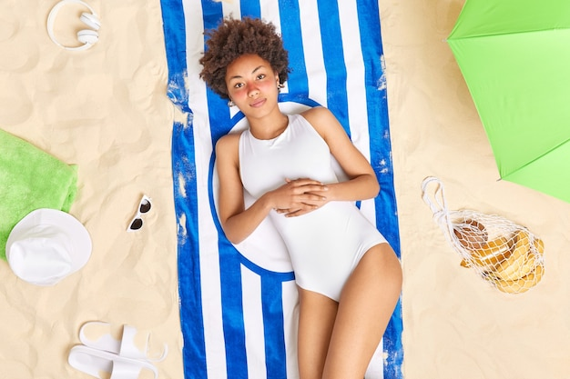 Mulher tem queimadura de sol tem rosto vermelho usa biquíni branco encontra-se na toalha listrada passa as férias na praia rodeada de itens diferentes, toma banho de sol por muito tempo. férias de verão