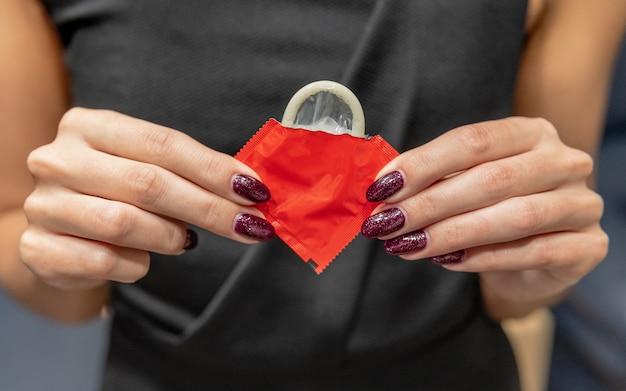 Mulher tem um preservativo nas mãos. o conceito de sexo seguro