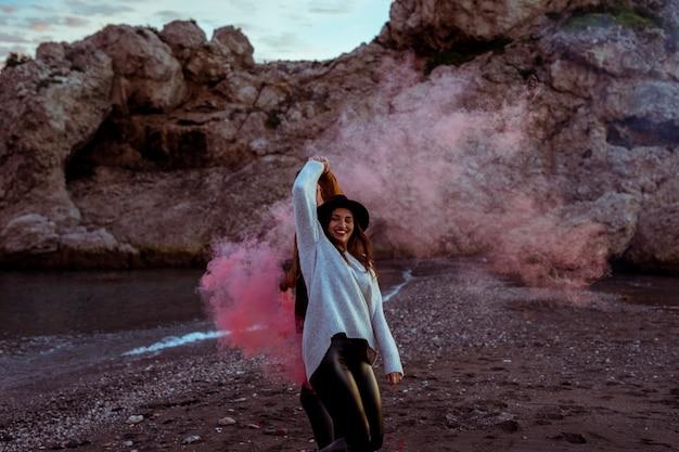 Mulher, tendo divertimento, com, bomba fumaça, ligado, costa mar