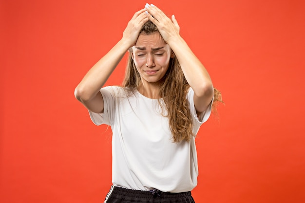 Mulher tendo dor de cabeça. isolado sobre pastel.
