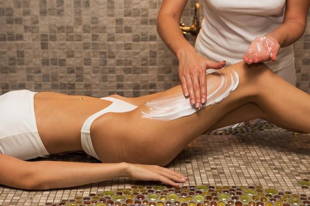 Mulher tendo massagem com creme no spa