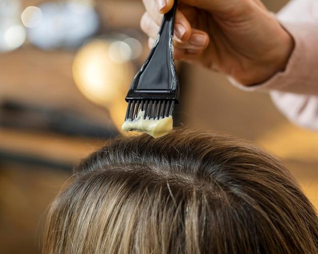 Mulher tendo o cabelo tingido em casa pelo cabeleireiro