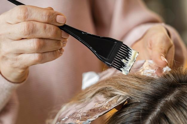 Mulher tendo o cabelo tingido em casa por esteticista