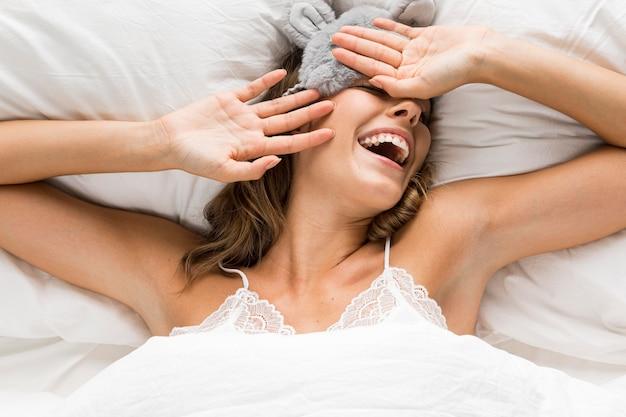 Mulher tendo um dia relaxante sentada na cama