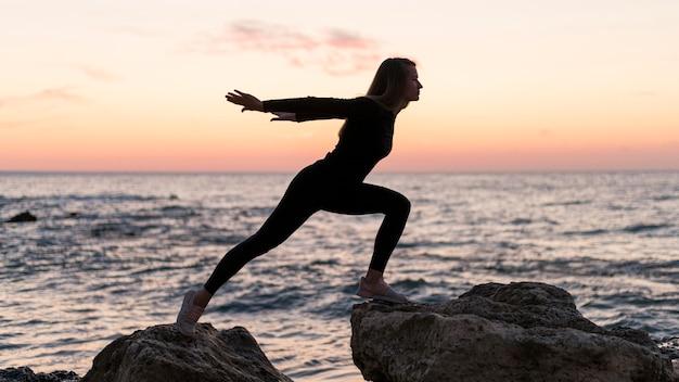 Mulher tendo uma posição desafiadora em uma costa
