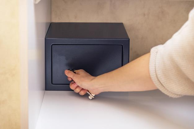 Mulher tenta abrir um cofre de metal seguro no quarto de hotel