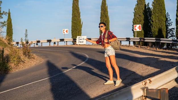 Mulher tenta parar o carro com placa de papelão, espaço de cópia. menina com rosto alegre, viajando de carona com a estrada no fundo. conceito de viagens e carona.