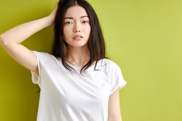 Mulher tenta se lembrar de algo, fica pensando em contemplação tocando no cabelo e olhando para a câmera, feminino em t-shirt casual isolado sobre o fundo verde do estúdio