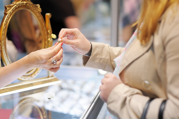 Mulher tentando alianças em um joalheiro, foco no anel