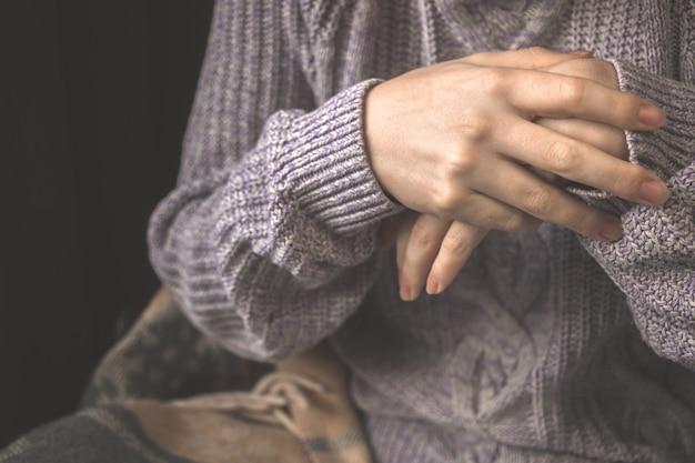 Mulher tentando aquecer as mãos, close-up de mãos frias, mulher em roupas de malha no inverno e foto do conceito de temporada de outono