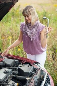 Mulher tentando consertar o carro