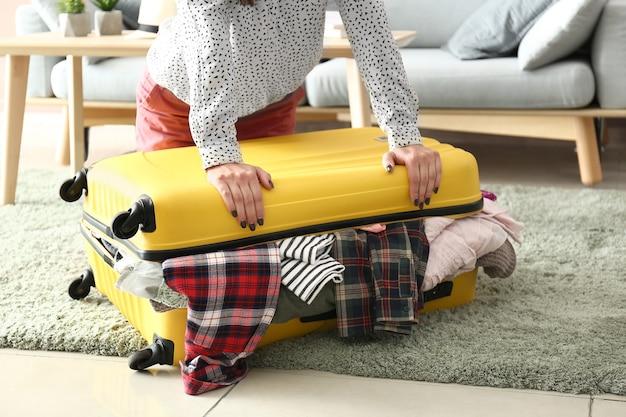 Mulher tentando fechar a mala com um monte de coisas.