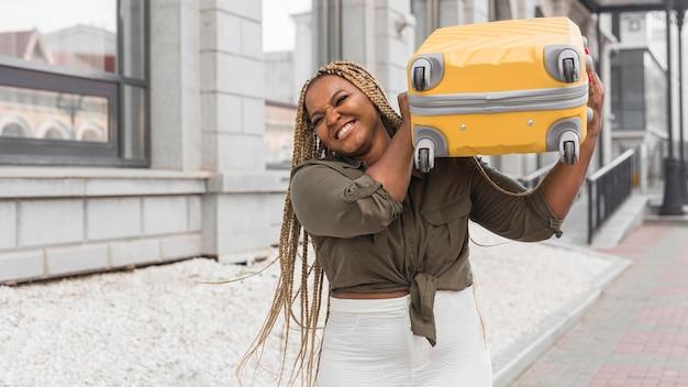 Mulher tentando levantar uma bagagem pesada no ombro
