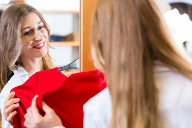 Mulher, tentando, moda, roupas, em, loja, espelho