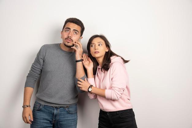 Mulher tentando ouvir o que o namorado está falando no telefone.