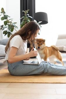 Mulher tentando trabalhar com seu cachorro por perto