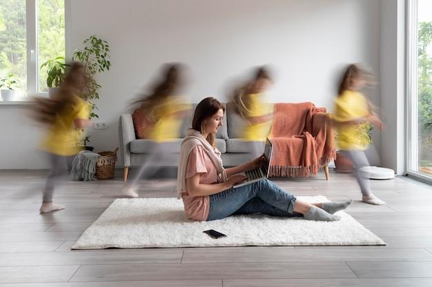Mulher tentando trabalhar em um laptop de casa enquanto os filhos estão correndo