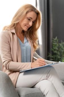 Mulher terapeuta escrevendo na prancheta