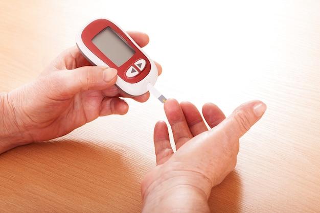 Mulher testando açúcar no sangue, close up das mãos