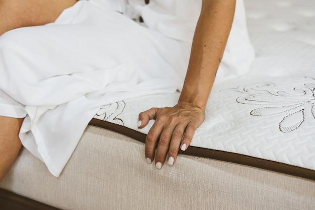 Mulher testando colchão em loja de móveis