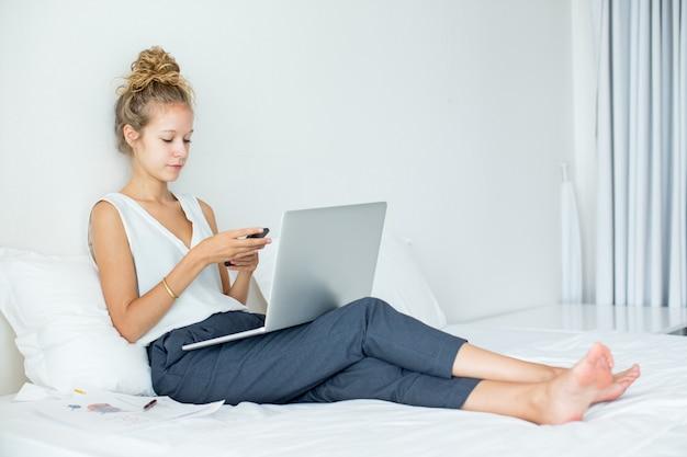 Mulher texting no smartphone na cama com laptop
