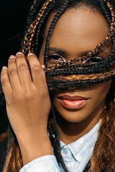 Mulher tímida afro-americana. humor estranho. jovem negra assustada, senhora introvertida em fundo escuro, conceito de timidez