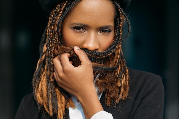 Mulher tímida afro-americana. segredos das mulheres. jovem negra assustada, problemas nos dentes, senhora introvertida em fundo escuro, conceito de silêncio