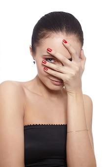 Mulher tímida, cobrindo o rosto com a mão, isolado no branco