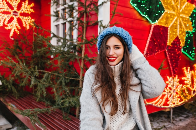 Mulher tímida com cabelos castanhos compridos, passando o tempo na feira de ano novo e posando perto de árvores verdes. foto ao ar livre da espetacular senhora caucasiana em pé de casaco cinza em decorações de natal vermelhas.