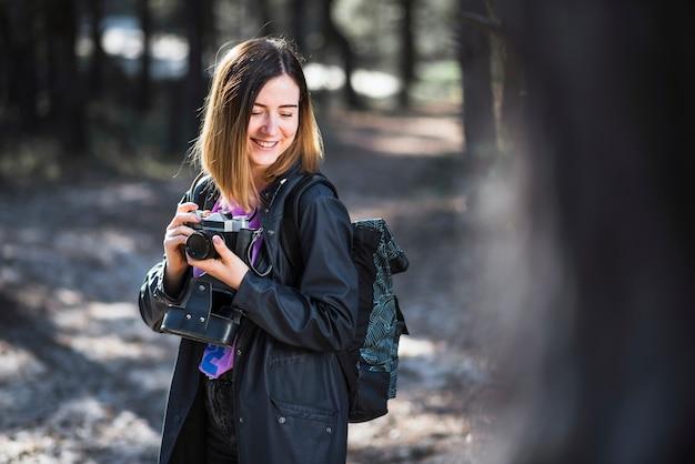 Mulher tímida com câmera na floresta Foto gratuita