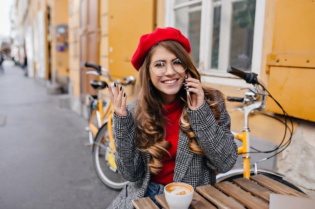 Mulher tímida com penteado encaracolado posando em um café ao ar livre com um sorriso no dia de setembro