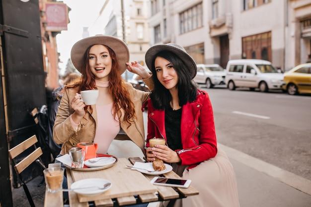Mulher tímida de saia bege posando com prazer em um café ao ar livre durante o almoço com um amigo