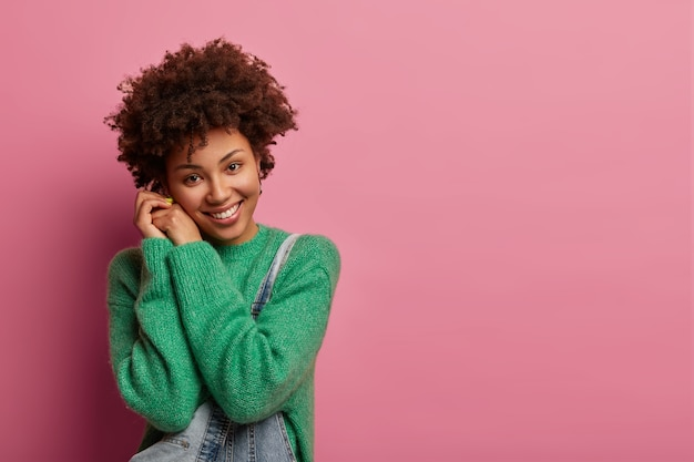 Mulher tímida e satisfeita com cabelo cacheado natural, sorriso gentil