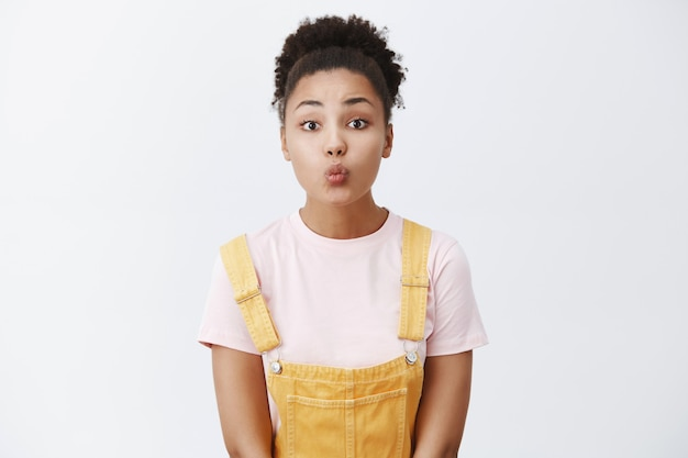 Mulher tímida esperando nervosamente pelo primeiro beijo, em pé em um macacão amarelo fofinho sobre a camiseta, dobrando os lábios para dar mwah, posando com ternura e feminilidade sobre a parede cinza