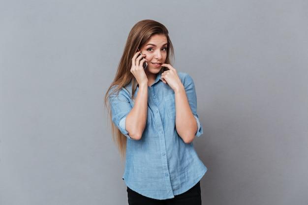 Mulher tímida na camisa falando no telefone