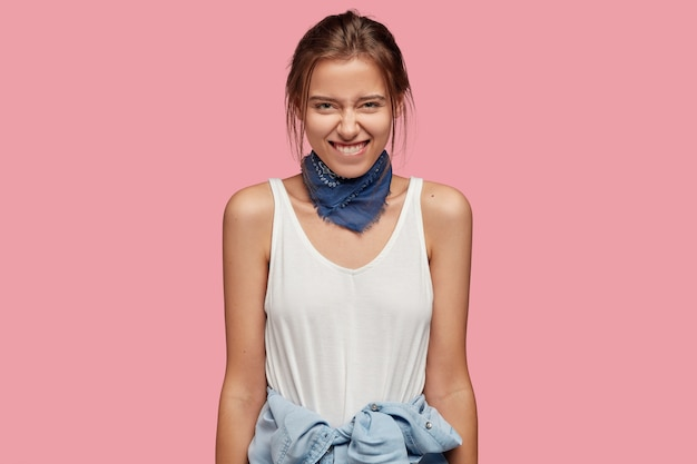 Mulher tímida positiva tem sorriso terno, morde o lábio inferior