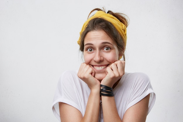 Mulher tímida satisfeita com olhos escuros, lenço amarelo na cabeça, mãos sob o queixo e expressão envergonhada