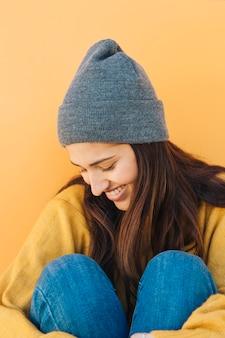 Mulher tímida usando chapéu sentado contra um fundo amarelo