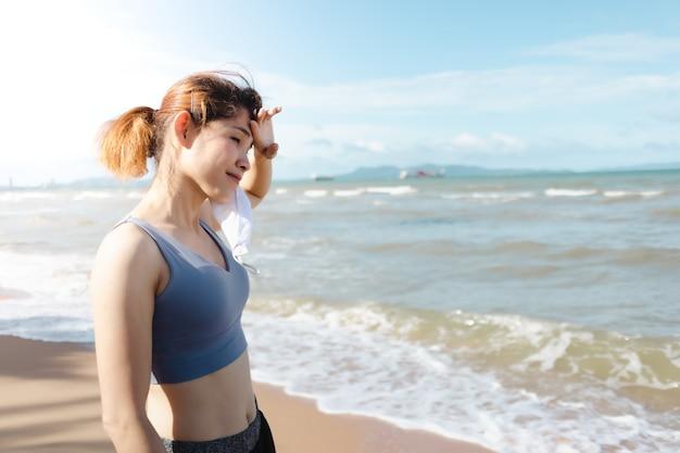 Mulher tira a máscara e descansa após terminar de correr na praia no verão