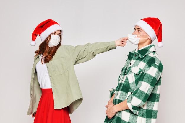 Mulher tira a máscara médica de um homem de fundo cinza do estúdio de natal