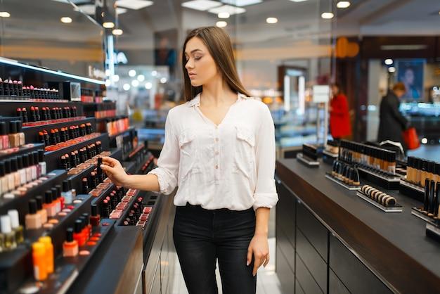 Mulher tira batom da prateleira da loja de cosméticos. comprador em vitrine em salão de beleza de luxo, cliente mulher no mercado de moda