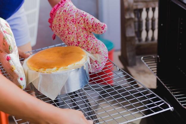 Mulher tira cheesecake basco queimado do forno.