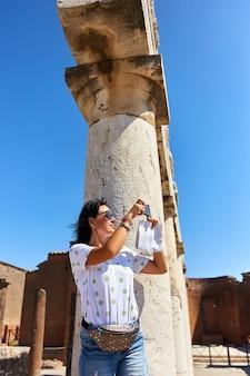 Mulher tira foto com smartphone no sítio arqueológico romano de pompéia, na itália