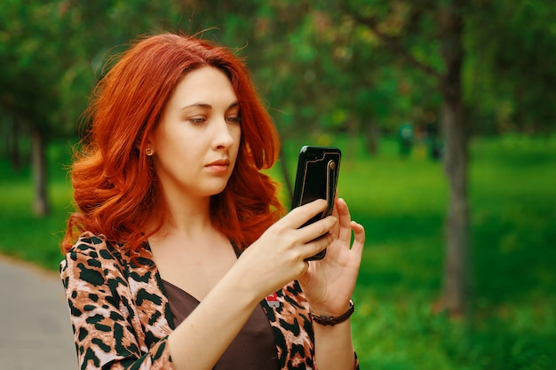 Mulher tira foto móvel na floresta