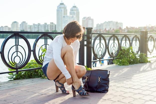 Mulher tira os sapatos. rio de fundo, estilo urbano.