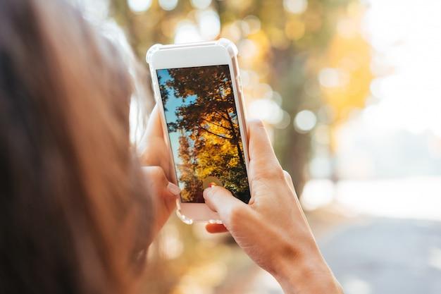 Mulher tira uma foto de uma árvore de outono na rua