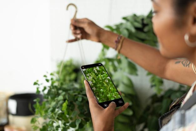 Mulher tira uma foto de uma planta de casa para compartilhar nas redes sociais