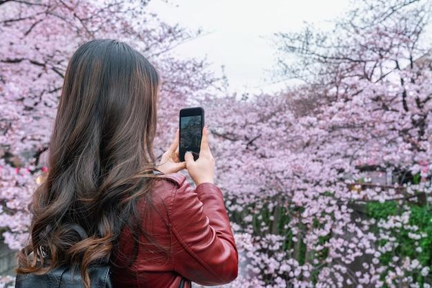 Mulher tira uma foto em flor de cerejeira ao longo do rio meguro, em tóquio, japão.