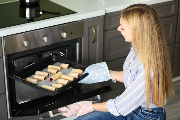 Mulher tirando a assadeira com massa caseira do forno