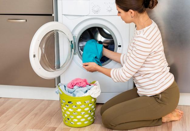 Mulher tirando a roupa na máquina de lavar roupa